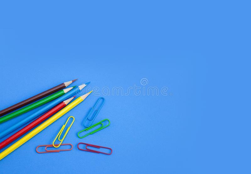 Conceptos de las fuentes de escuela, lápices multicolores y clips en fondo azul imagenes de archivo