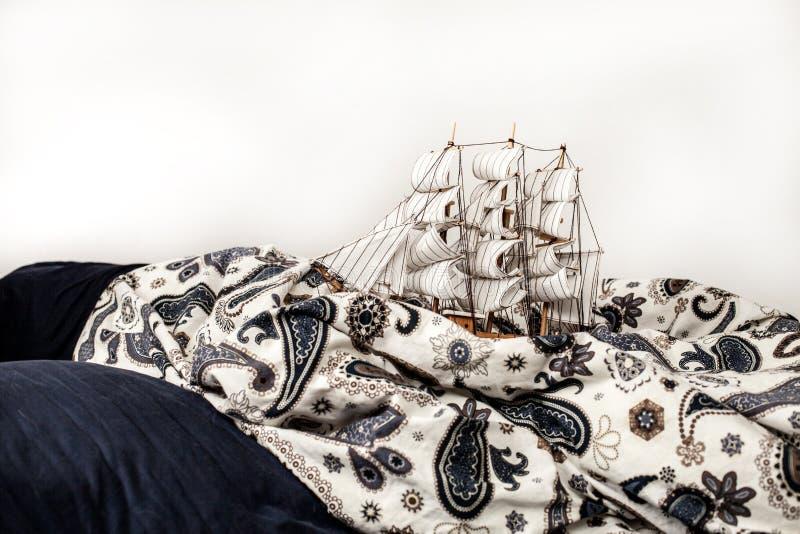 Conceptos de negocio y de creatividad modelo de un velero en un lecho azul Sueño extraño imágenes de archivo libres de regalías