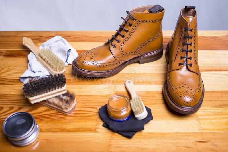 Conceptos del calzado Primer de Tan Brogue Boots Along superior con el sistema de la limpieza fotos de archivo