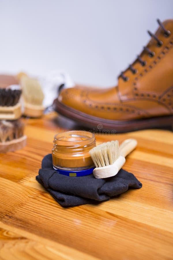 Conceptos del calzado Primer de Tan Brogue Boots Along superior con las herramientas de la limpieza fotografía de archivo libre de regalías