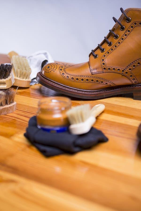 Conceptos del calzado Primer de Tan Brogue Boots Along superior con los accesorios de la limpieza fotografía de archivo libre de regalías