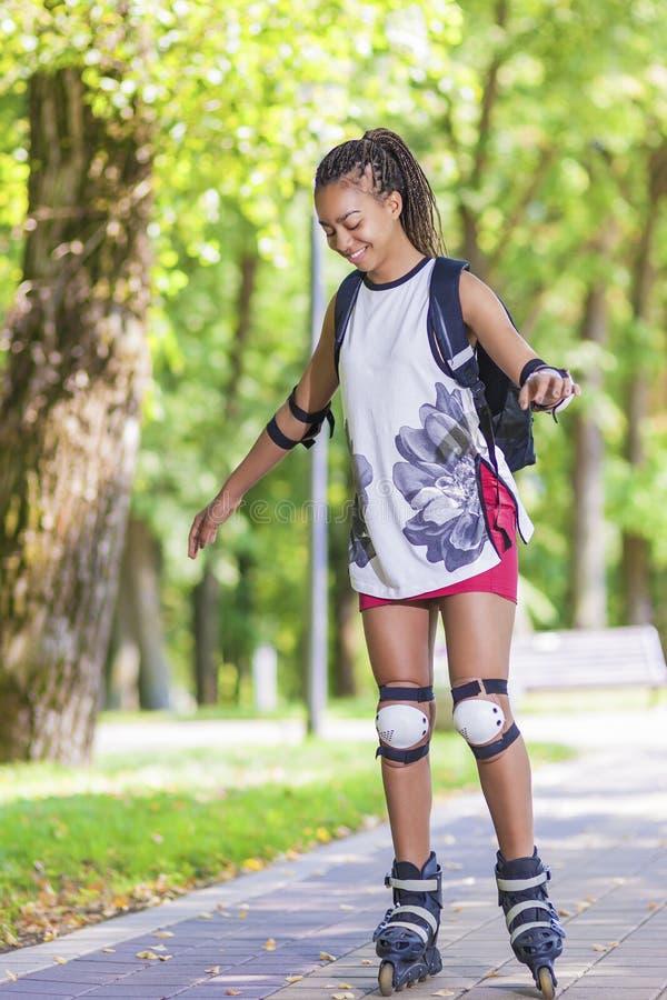 Conceptos del deporte Adolescente afroamericano joven que aprende patinaje sobre ruedas en área del parque foto de archivo