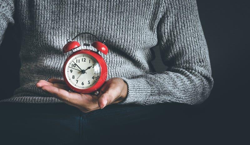 Conceptos del tiempo y de la vida con el despertador de la tenencia del hombre joven y el sentarse en el sofá Imágenes de la moti foto de archivo
