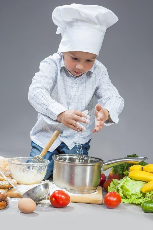 Concepts de cuisine Portrait du fonctionnement caucasien concentré de garçon photographie stock libre de droits