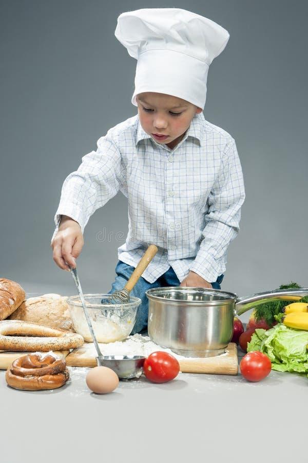 Concepts de cuisine Portrait de garçon caucasien concentré image libre de droits