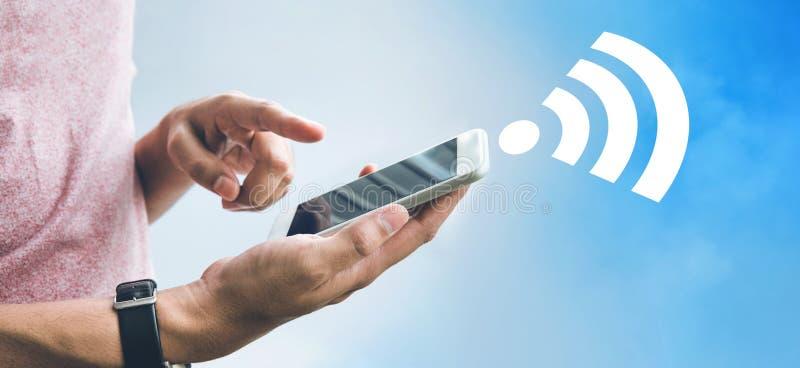 Concepts de wifi d'Internet avec le smartphone, le mobile et l'icône masculins de participation de main sur le fond de ciel photos stock