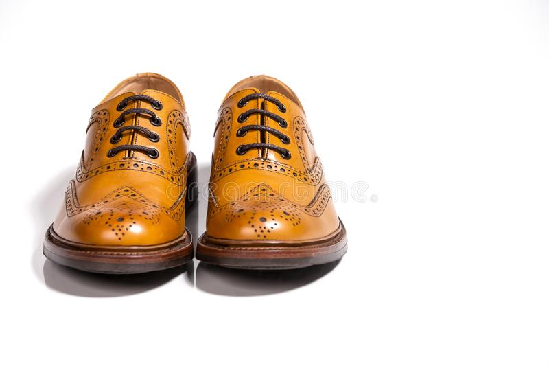 Concepts of Luxury Male Footwear. Full Broggued Tan Leather Oxfords. Shoes Isolated Over White Background. Horizontal Image stock images