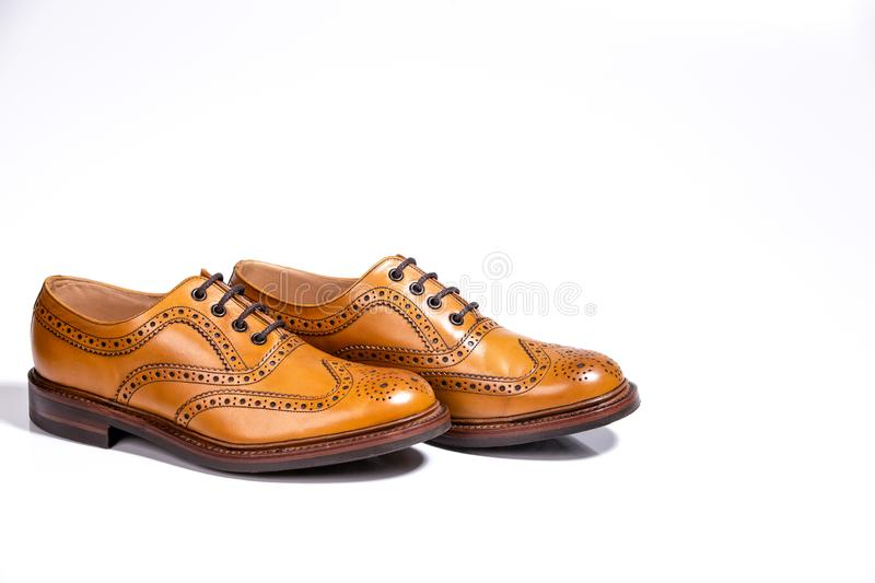 Pair of Full Broggued Tan Leather Shoes. Concepts of Luxury Male Footwear. A pair of Full Broggued Tan Leather Oxfords Shoes Isolated Over White Background royalty free stock image