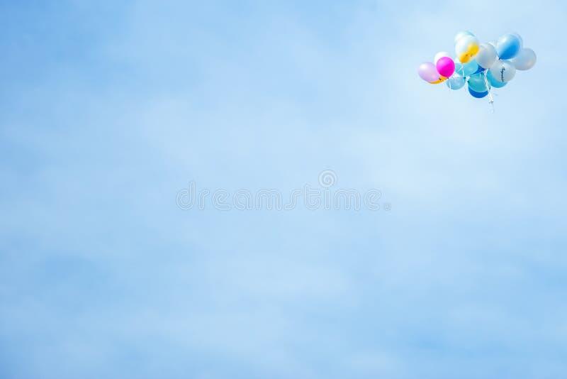 Many small flying balloon in education celebration fair on the blue sky. royalty free stock photos