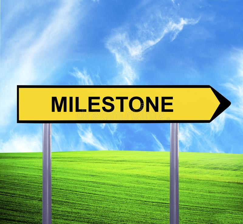 Conceptual arrow sign against beautiful landscape with text - MILESTONE royalty free stock images