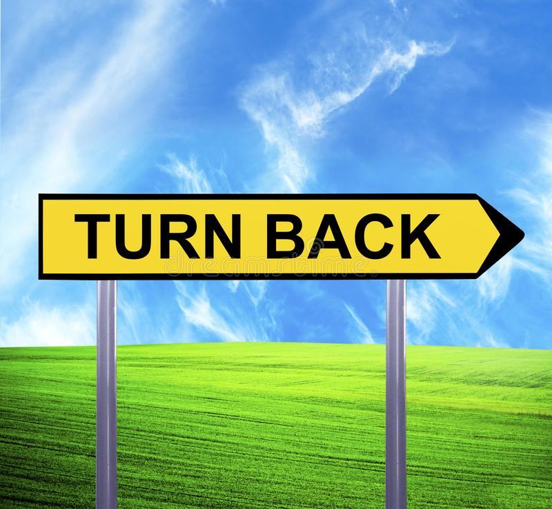 Conceptual arrow sign against beautiful landscape with text - TURN BACK stock photos