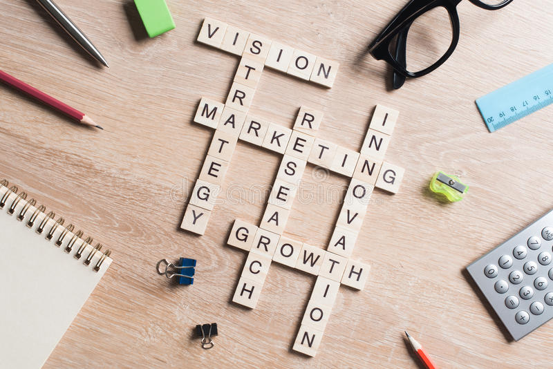 Conceptual business keywords on table with elements of game making crossword. Words of business marketing collected in crossword with wooden cubes royalty free stock photo