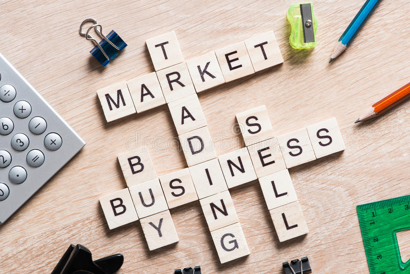 Conceptual business keywords on table with elements of game making crossword. Words of business marketing collected in crossword with wooden cubes royalty free stock images