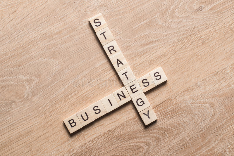 Conceptual business keywords on table with elements of game making crossword. Words of business strategy collected in crossword with wooden cubes stock image