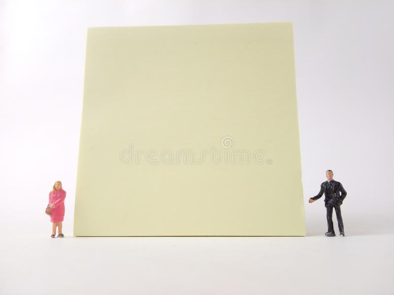 Conceptual Businessman and Woman doing Presentation, near at big blank Yellow paper, at white backround royalty free stock photos