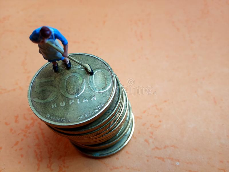 Conceptual Close Up Illustration for Money Laundry Activity, worker mini figure toy clean 500 hundred rupiah golden indonesia coin stock photo