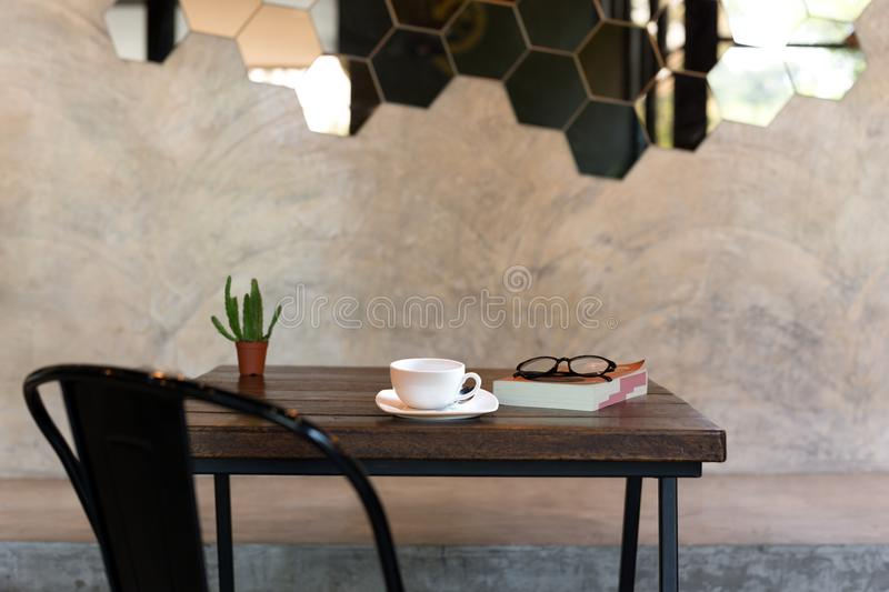 Conceptual coffee cup with book and glasses and green plant on. Wooden table with black chair stock images