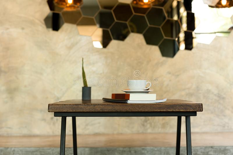 Conceptual coffee cup on top of book with green plant. On wooden table royalty free stock photo