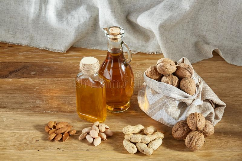 Conceptual composition of glass oil jars with different kinds of nuts on wooden table, close-up. royalty free stock photo