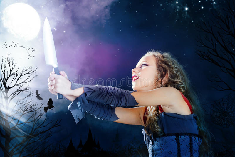 Conceptual crazy haunted girl at halloween. Close up portrait of young female vampire holding big knife. Castle towers and crows flaying in full moon background stock photo