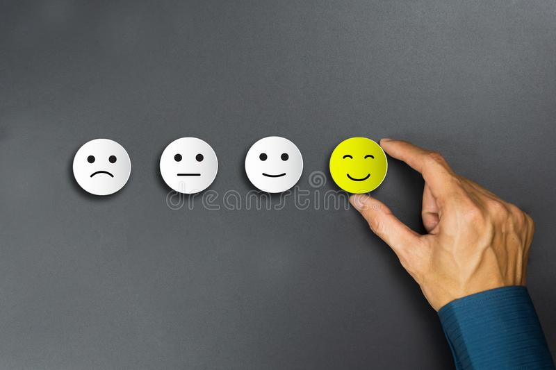 Conceptual the customer responded to the survey. The client using hand choose happy face smile icon. Depicts that customer is very. Satisfied. Service royalty free stock images