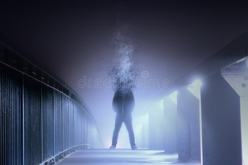 A conceptual digital art picture of a man who`s head has disintegrated and turned into smoke, standing on a foggy path at night. W stock images