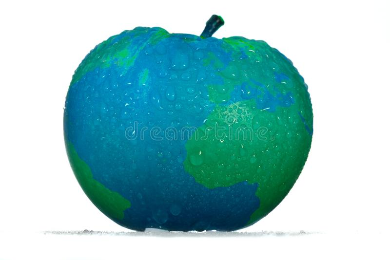 Conceptual eco-friendly apple with drops in a designer blue color with green continents of the globe map. Conceptual eco-friendly apple with water drops in a royalty free stock photo