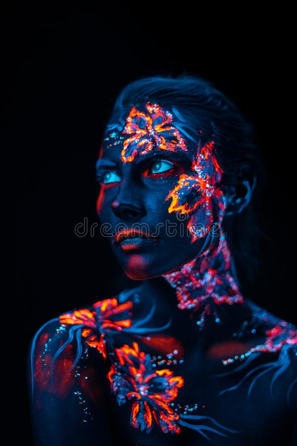 Beautiful flowers in UV light on a young girl face and body royalty free stock photography