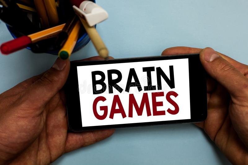 Conceptual hand writing showing Brain Games. Business photo showcasing psychological tactic to manipulate or intimidate with oppon. Ent Man holding cell phone royalty free stock photo