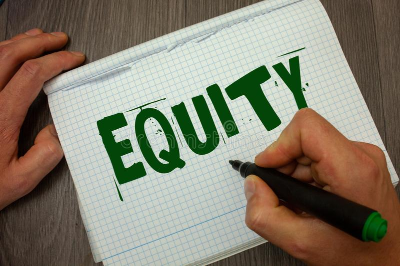 Conceptual hand writing showing Equity. Business photo text Value of a company divided into equal parts owned by shareholders Man. Hold holding black marker stock photos