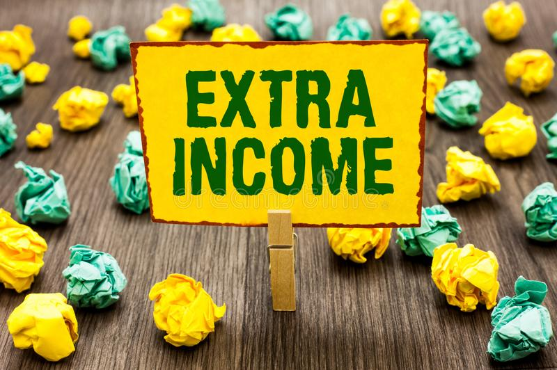 Conceptual hand writing showing Extra Income. Business photo text Additional fund received or earned from a non regular basis Clot. Hespin holding yellow note stock photography