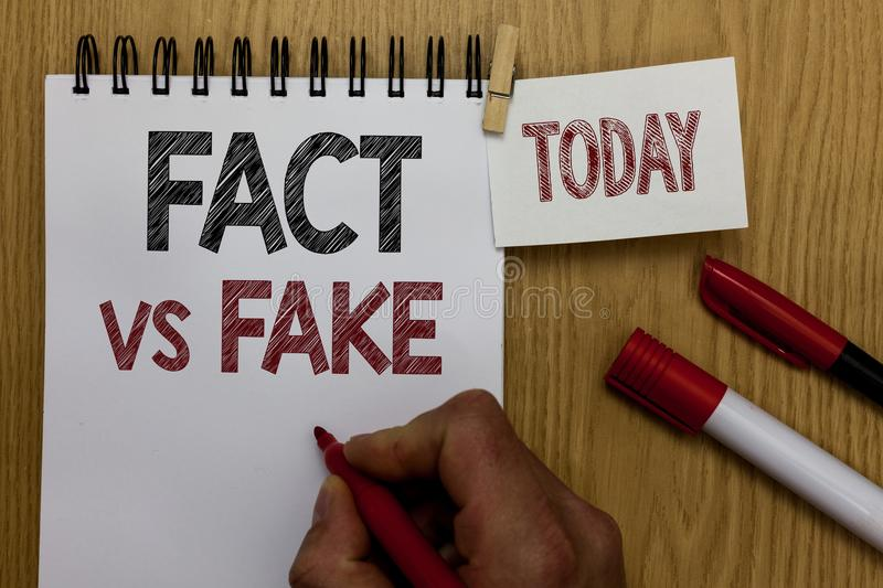 Conceptual hand writing showing Fact Vs Fake. Business photo text Rivalry or products or information originaly made or imitation M. An holding marker notebook royalty free stock photos