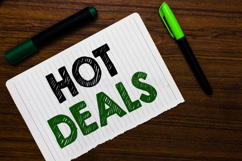 Conceptual hand writing showing Hot Deals. Business photo text An agreement through which one of the paties is offered and accept. Notebook paper markers wooden royalty free stock photography