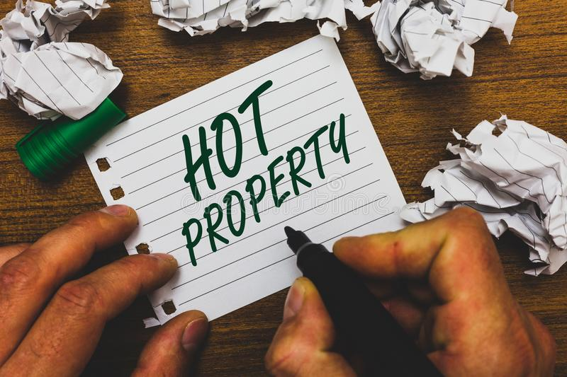Conceptual hand writing showing Hot Property. Business photo text Something which is sought after or is Heavily Demanded Man holdi stock image