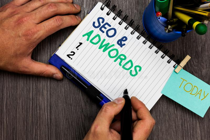Conceptual hand writing showing Seo and Adwords. Business photo showcasing Pay per click Digital marketing Google Adsense Man hold. Ing marker notebook reminder royalty free stock photography