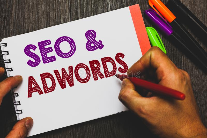 Conceptual hand writing showing Seo and Adwords. Business photo text Pay per click Digital marketing Google Adsense Man holding no. Tebook paper communicating stock photos