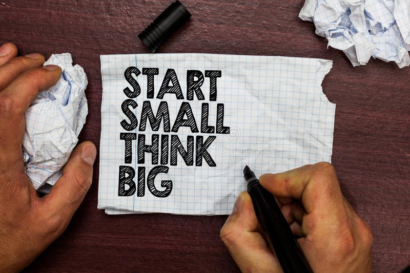 Conceptual hand writing showing Start Small Think Big. Business photo text Initiate with few things have something great in mind H. And hold pen sketch word on royalty free stock image