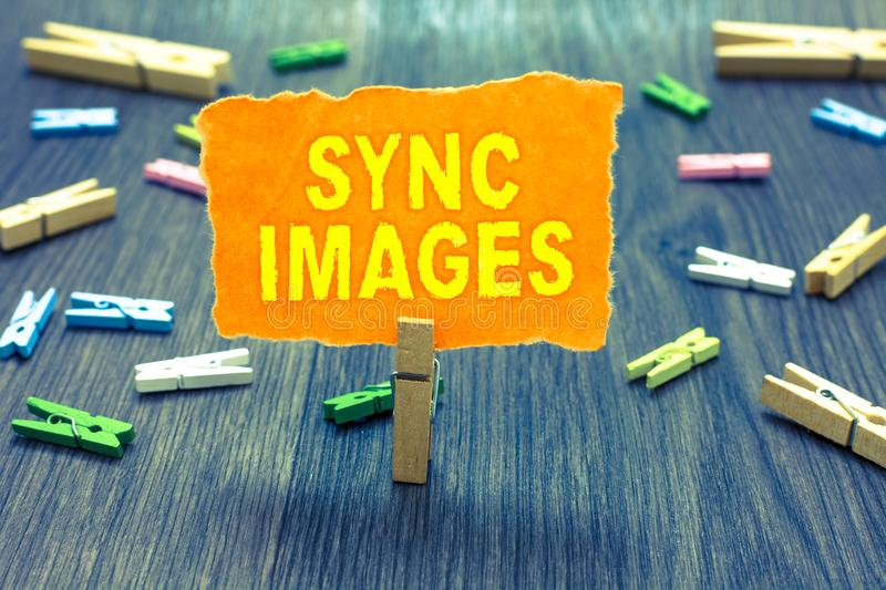 Conceptual hand writing showing Sync Images. Business photo text Making photos identical in all devices Accessible anywhere Clothe. Spin holding orange paper stock photo