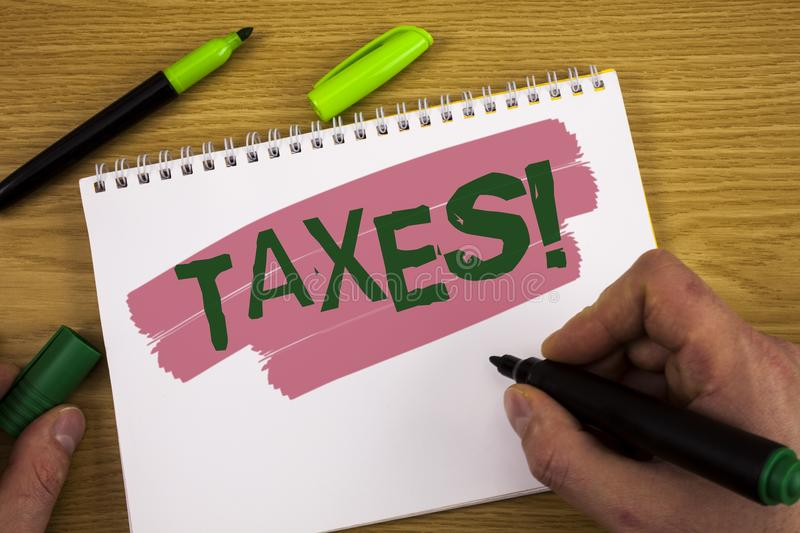Conceptual hand writing showing Taxes Motivational Call. Business photo text Money demanded by a government for its support writte. N by Man Notepad holding stock photography