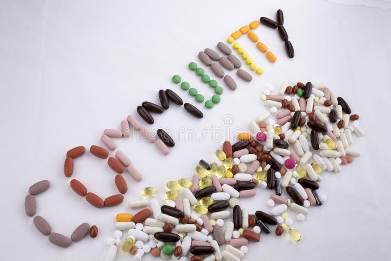 Conceptual Hand writing text caption inspiration Medical care Health concept written with pills drugs capsule word community On wh. Ite background with space royalty free stock photos