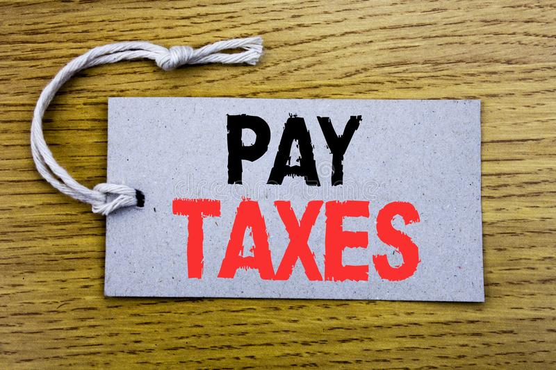 Conceptual hand writing text caption showing Pay Taxes. Business concept for Taxation Overtax Return written on price tag paper wi. Th copy space on wooden stock photography