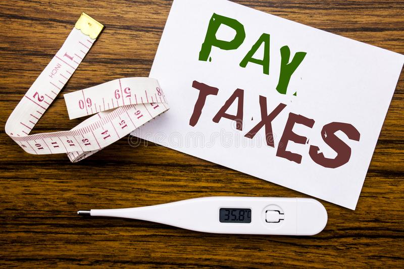 Conceptual hand writing text caption showing Pay Taxes. Business concept for Taxation Overtax Return written on sticky note paper. Wood background. Meter and royalty free stock photography