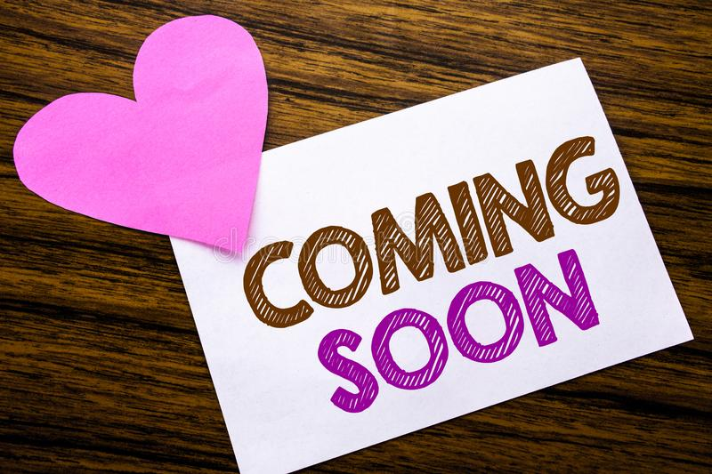 Conceptual hand writing text showing Coming Soon. Concept for Message Future written on sticky note paper, wooden wood background. Conceptual hand writing text royalty free stock photo