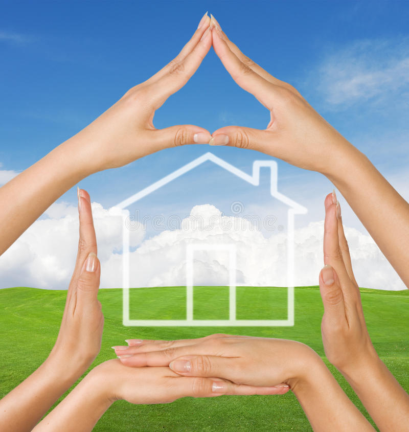 Conceptual home symbol. Female hands showing conceptual home symbol over summer landscape background stock image