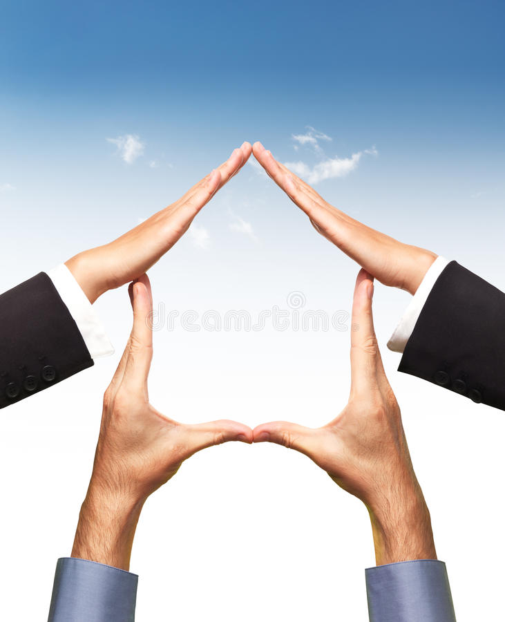 Conceptual home symbol made by hands over blue sky. Conceptual home symbol made by hands in a shape of a house over blue sky and white background. Real estate stock photo