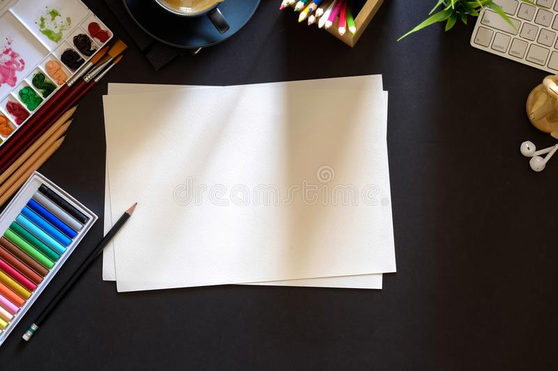 Conceptual image of Artist graphic designer workplace dark surface table. Designer workspace top view with essential elements on dark wooden board stock photo