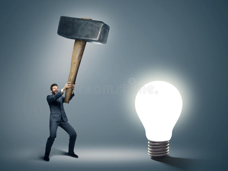 Conceptual image of a businessman holding huge hammer stock images