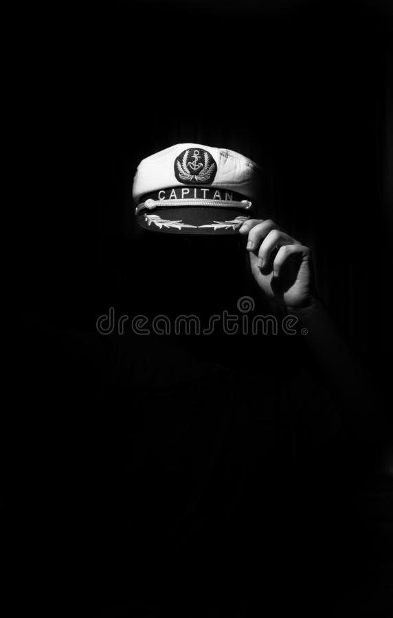 Conceptual image about captain's hat and one hand in the dark royalty free stock photo