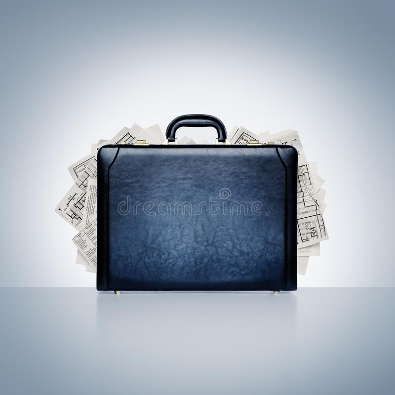 Black leather briefcase overflowing with plans, reports, and paperwork. Intellectual property and data. Conceptual image of classic black leather briefcase stock image