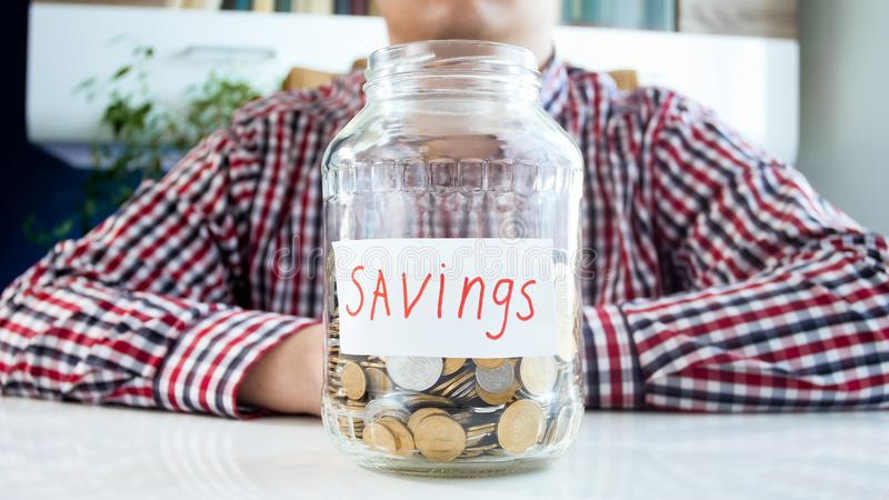 Conceptual photo of family budget. Man with full glass jar for savings royalty free stock photos
